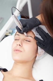 Schoonheidsspecialist brengt permanente make-up aan op wenkbrauwen