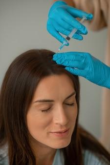 Schoonheidsspecialist die collageen injecteert in het gezicht van haar cliënt