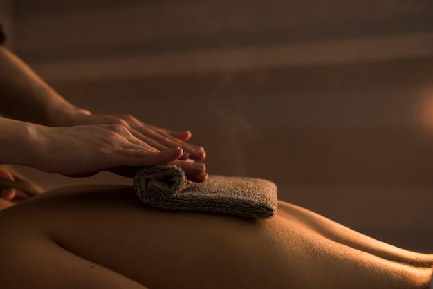 Schoonheidsspecialist die de rug van de vrouw met hete handdoek masseert