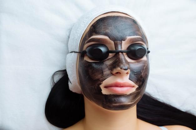 Schoonheidsspecialist die een zwart masker toepast op het gezicht van een mooie vrouw met zwarte handschoenen, een prachtige vrouw in de spa h