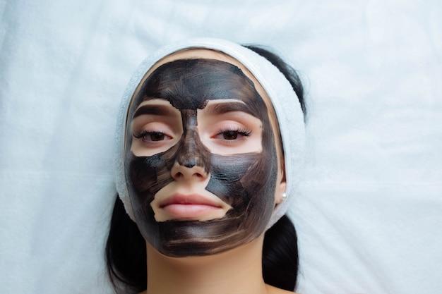 Schoonheidsspecialist die een zwart masker toepast op het gezicht van een mooie vrouw met zwarte handschoenen, een prachtige vrouw in de spa