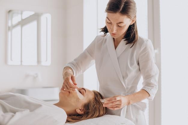 Schoonheidsspecialist die gezichtsbehandeling doet en gezichtsmasker toepast