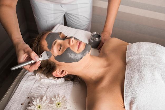 Schoonheidsspecialist die gezichtsmasker met borstel op het gezicht van de vrouw toepast