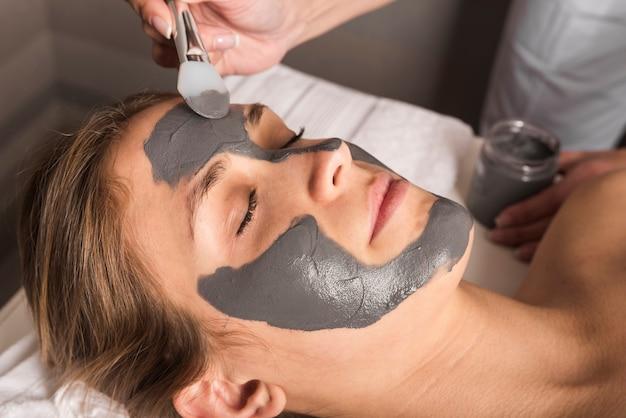 Schoonheidsspecialist die gezichtsmasker op het gezicht van de jonge vrouw toepast