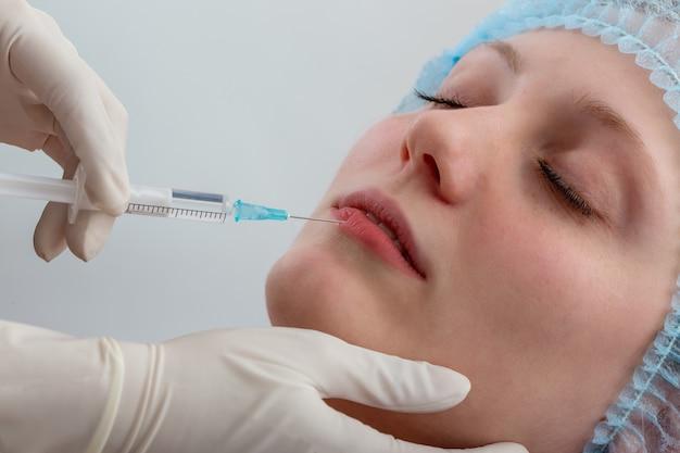 Schoonheidsspecialist die lippen van vrouw vult met vloeistof in close-up