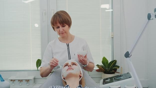 Schoonheidsspecialist die roommasker op het gezicht van de vrouw zet bij schoonheidssalon