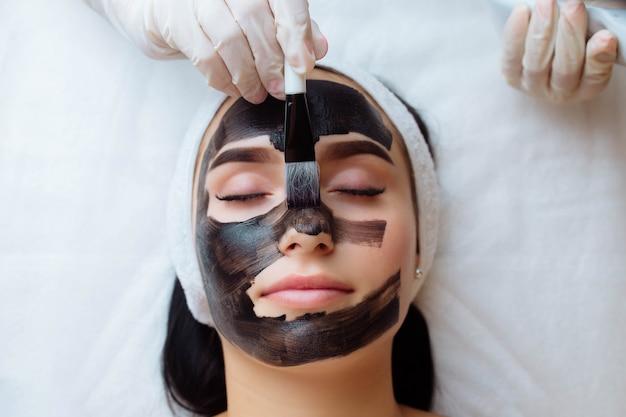 Schoonheidsspecialist die zwart masker op het gezicht van de mooie vrouw toepast met zwarte handschoenen prachtige vrouw in spa ha...