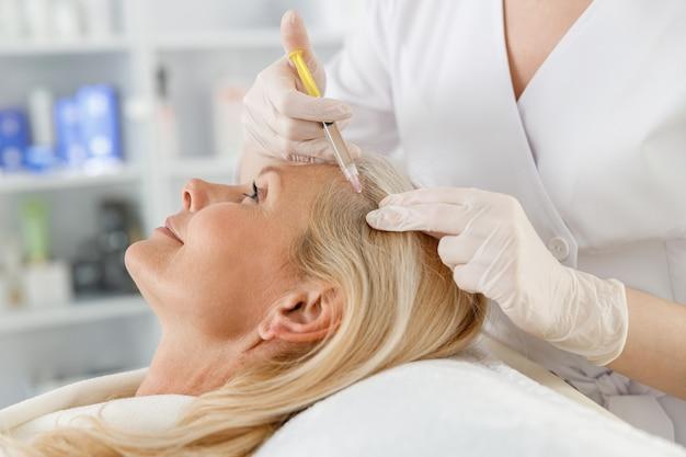 Schoonheidsspecialist doet prp-therapie tegen haaruitval van een oudere blonde vrouw in een schoonheidssalon.
