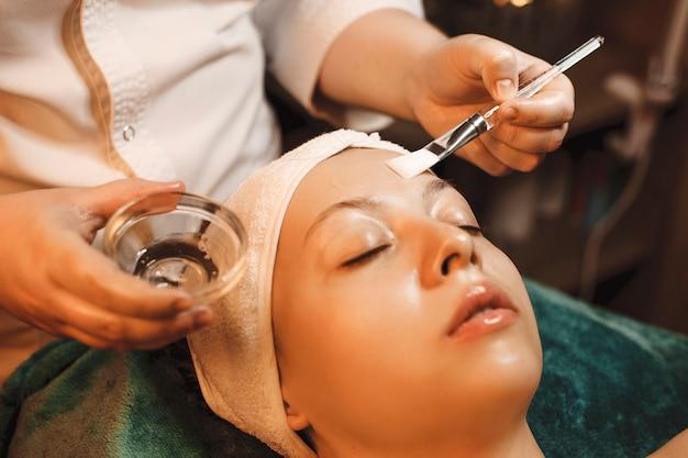 Schoonheidsspecialist en een transparant masker met hyaluronzuur toepassen op een vrouw in een spa-salon.