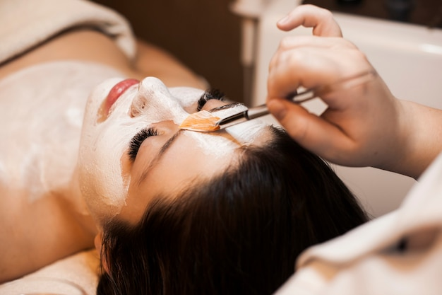Schoonheidsspecialist hand witte huidverzorging masker toe te passen op een mooi vrouwelijk gezicht in een wellnessresort