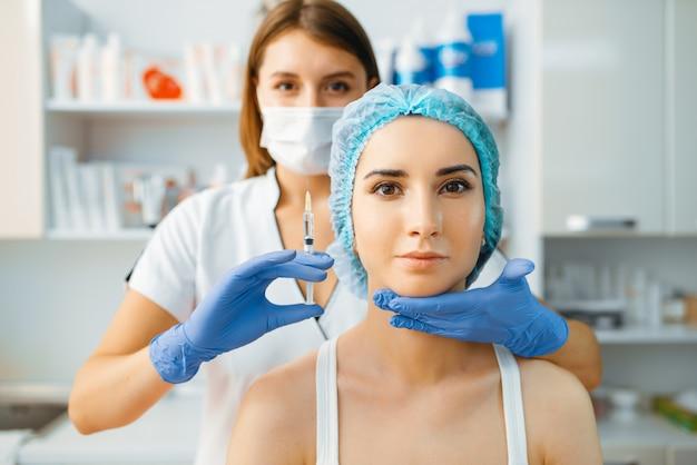 Schoonheidsspecialist houdt spuit met injectie van botox op het gezicht van de vrouwelijke patiënt.
