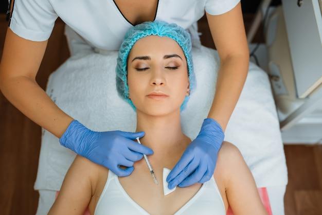 Schoonheidsspecialist in handschoenen geeft botox injectie aan vrouwelijke patiënt op behandeltafel, bovenaanzicht.