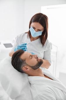 Schoonheidsspecialist in masker werkt met patiënt van middelbare leeftijd bij voorhoofdvullerprocedure in salon