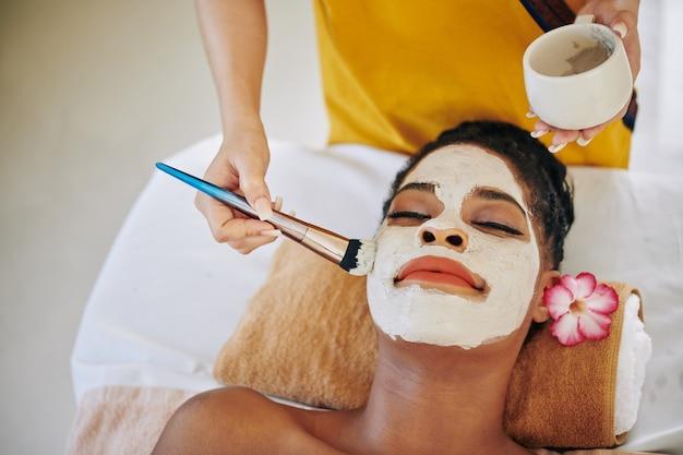 Schoonheidsspecialist met behulp van borstel bij het aanbrengen van matterende modder masker op gezicht van mooie jonge vrouw