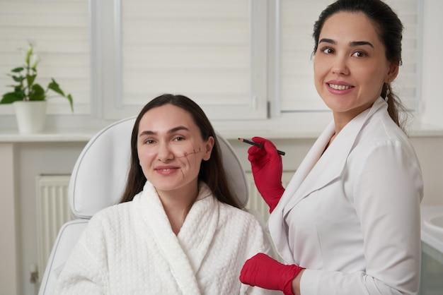 Schoonheidsspecialist met behulp van gezichtsmarkering op het gezicht van de patiënt vóór schoonheidsbehandeling in de spa salon