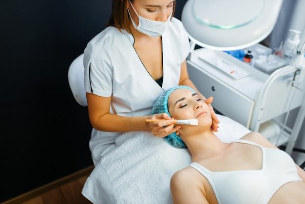Schoonheidsspecialist met borstel reinigt gezichtshuid aan vrouwelijke patiënt, botox-voorbereiding. verjongingsprocedure in schoonheidsspecialiste salon.