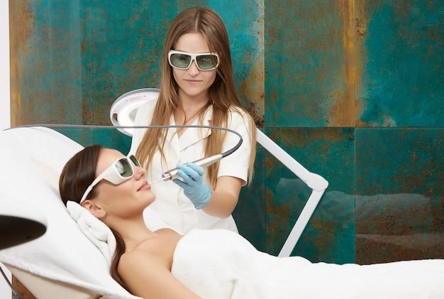 Schoonheidsspecialist met laser in de buurt van het gezicht van de vrouwelijke klant die een witte en beschermingsbril draagt