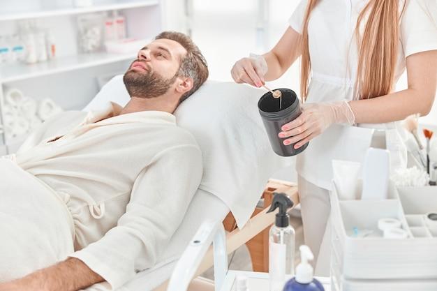 Schoonheidsspecialist neemt suikerpasta uit blik in was. concept van geneeskunde, medische instrumenten, gezondheidszorg, schoonheidsindustrie, ontharing.