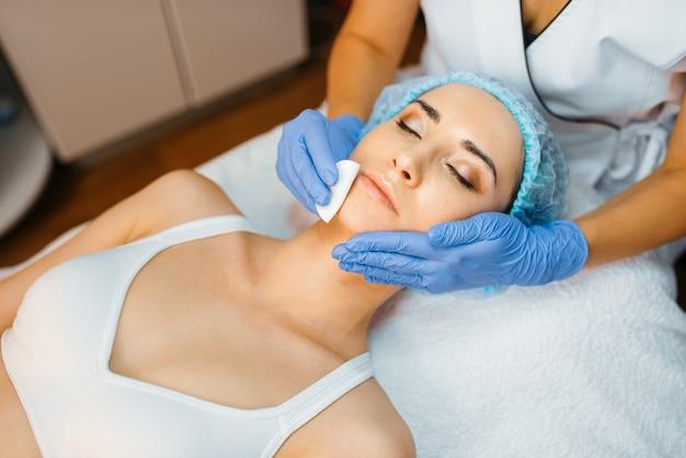 Schoonheidsspecialist reinigt de gezichtshuid aan vrouwelijke patiënt.