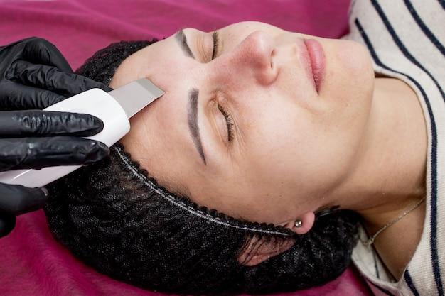 Schoonheidsspecialist, schoonheidsspecialiste die gezichtsbehandeling maakt met ultrasone spatel voor jonge vrouw, gezichtshuid scrubber behandeling met ultrasone spatel, gezichtsreinigingsprocedure in schoonheidssalon.
