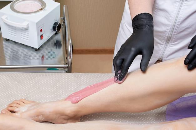 Schoonheidsspecialist schoonheidsspecialiste waxen vrouwelijke benen in het spa-centrum schoonheidssalon cosmetologie concept