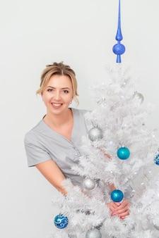 Schoonheidsspecialist staande en glimlachend in de buurt van de kerstboom
