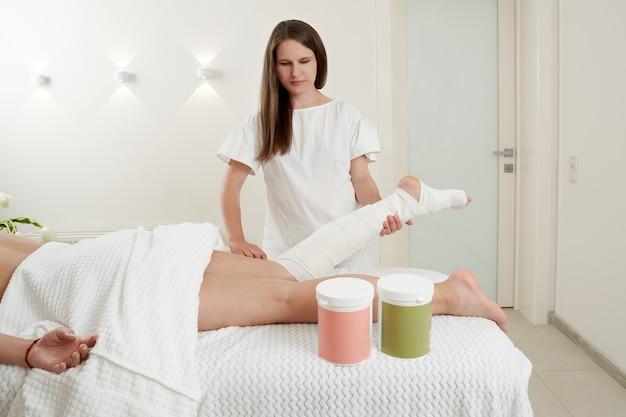 Schoonheidsspecialist wikkelt het been van de klant anticellulitis procedure van styx inpakken en banding