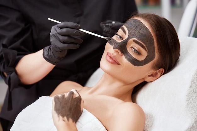 Schoonheidsspecialist zwart masker toe te passen op het gezicht van de vrouw, het dragen van zwarte handschoenen, prachtige vrouw in spa met gezichtsprocedures