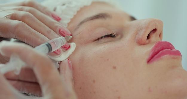 Schoonheidsspecialiste arts maakt injecties in de huid van het gezicht van een jonge mooie vrouw. gezicht mesotherapie procedure in een schoonheidssalon. mesotherapie, biorevitalisatie.