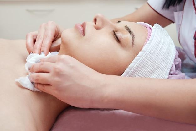 Schoonheidsspecialiste arts reinigt de huid van een jonge vrouw