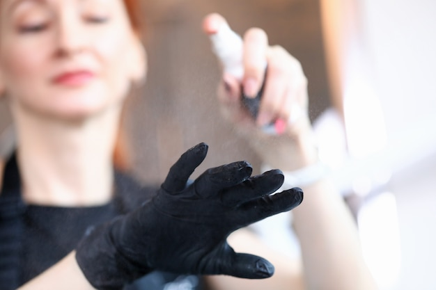 Schoonheidsspecialiste behandelt handenhandschoenen met een antisepticum. salon procedure. vrouwelijke make-up artist werk