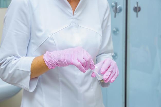 Schoonheidsspecialiste bereidt een peeling in een container voor maatregelen voor het aanbrengen op een gezicht