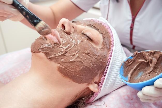 Schoonheidsspecialiste brengt met een kwast een voedend masker op het gezicht aan