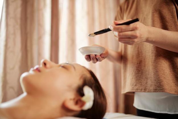 Schoonheidsspecialiste crème gezichtsmasker toe te passen