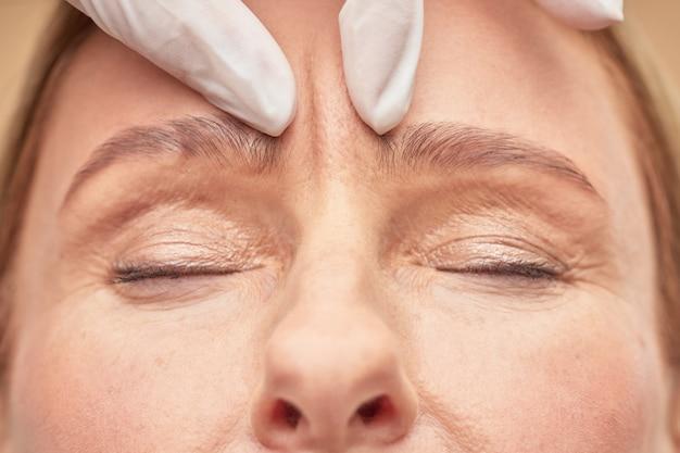 Schoonheidsspecialiste die de conditie van de vrouwelijke huid controleert