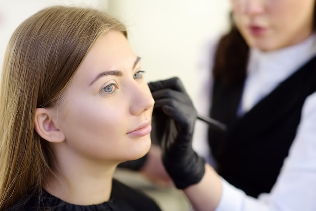 Schoonheidsspecialiste die de toon van de stichting toepast met behulp van een speciale borstel op het jonge mooie model gezicht. gezichtsverzorging en make-up