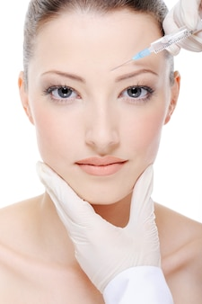 Schoonheidsspecialiste die een injectie geeft op het jonge vrouwelijke gezicht