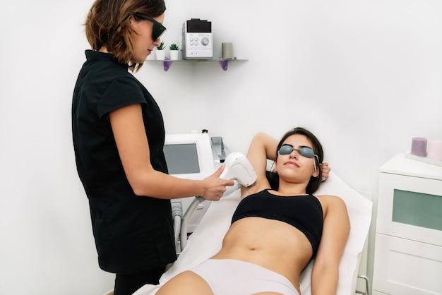 Schoonheidsspecialiste die een laserdiodebehandeling geeft aan een vrouw in de oksel waar ze een laserbeschermingsbril draagt