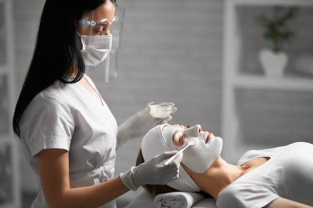 Schoonheidsspecialiste die gezicht met schoonheidsmiddelen voor patiënt schoonmaakt