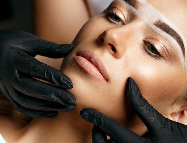 Schoonheidsspecialiste die het gezicht van de jonge vrouw vasthoudt voor permanente make-up in schoonheidssalon