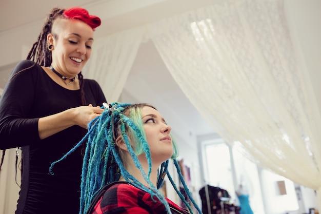 Schoonheidsspecialiste die het haar van klanten stylt