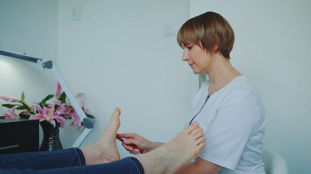 Schoonheidsspecialiste die shiatsu-voetmassage maakt met behulp van een toverstaf