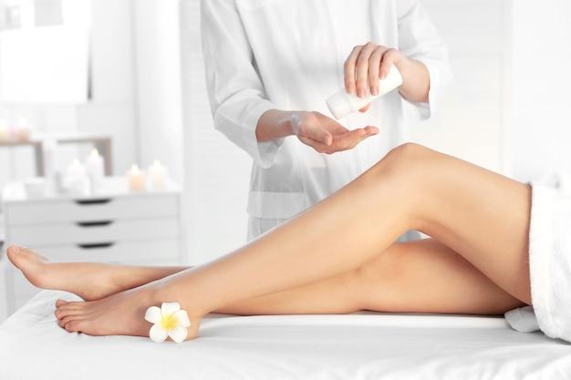 Schoonheidsspecialiste die vochtinbrengende crème aanbrengt op vrouwelijke benen in het kuuroord