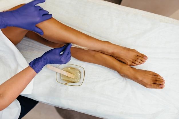Schoonheidsspecialiste die vrouwelijke benen in kuuroordcentrum in de was zet