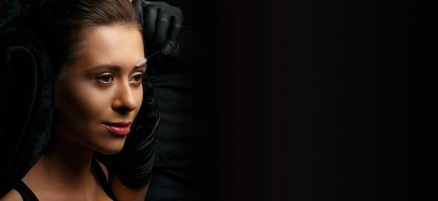 Schoonheidsspecialiste die wenkbrauwen voorbereidt op een permanente pigmentatieprocedure. lege ruimte