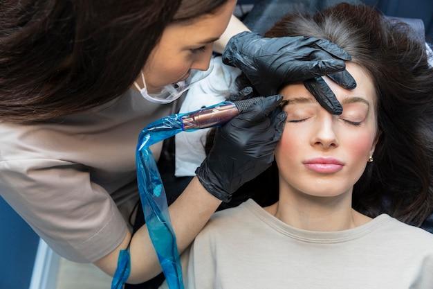 Schoonheidsspecialiste doet een wenkbrauwbehandeling voor haar cliënt