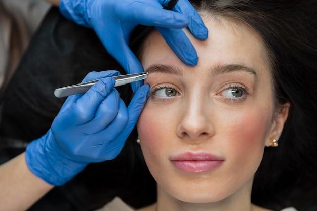Schoonheidsspecialiste doet een wenkbrauwbehandeling voor haar vrouwelijke cliënt
