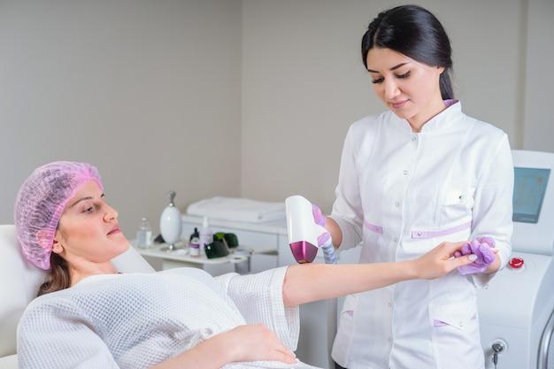 Schoonheidsspecialiste doet epileren op mooie vrouwelijke hand in medisch centrum. vrouw die laserhaar ontvangt