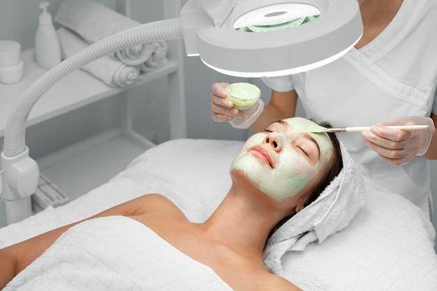 Schoonheidsspecialiste gezichtsmasker toe te passen op vrouwelijke cliënt