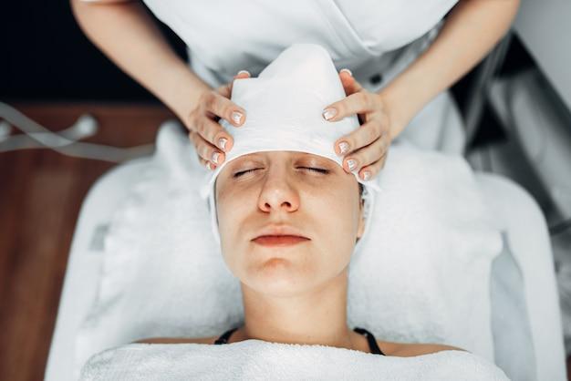 Schoonheidsspecialiste handen op vrouwelijk patiënt gezicht, bovenaanzicht